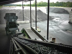 Aufgabetrichter und Förderband zur überdachten Aufbereitungsanlage vom Hallenaußenbereich mit den umliegenden Kohle Lagerboxen